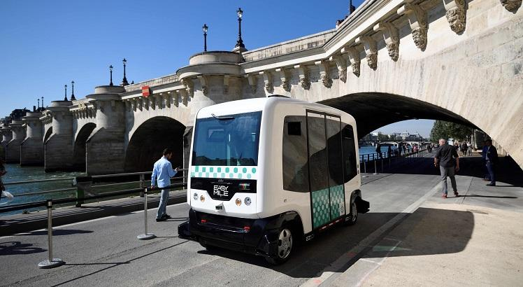 People watch a French capital's transport authority RATP electric-powered driverless EZ10 minibus, able to carry up to 12 passengers, carrying out its first test on the banks of the river Seine unde rthe Pont-Neuf bridge on September 24, 2016 in Paris.    The RATP carries out its first test of a driverless minibus, in the hope that regular routes for the hi-tech vehicles will be up and running within two years. One of the self-driving shuttle buses, made by French hi-tech firm Easymile,  run today along a special circuit in Paris on a pedestrianised street near the River Seine. / AFP / ERIC FEFERBERG